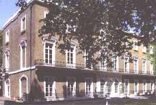 Image of a historic buildings with lots of windows across and a tree covering part of the image.